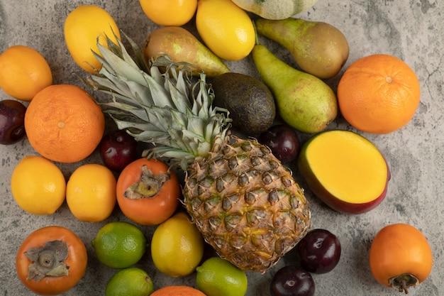 Asortyment kompozycji świeżych dojrzałych owoców na marmurowej powierzchni.