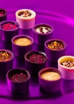 Asortyment luksusowych białych i ciemnych cukierków czekoladowych na fioletowym talerzu