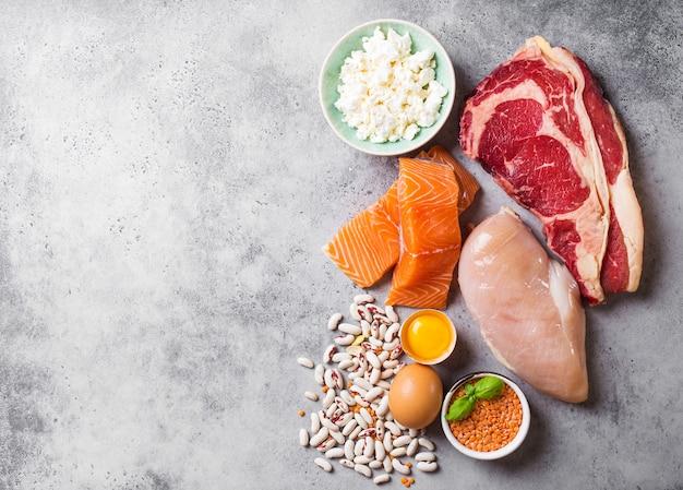 Asortyment naturalnych źródeł białka z żywności: mięso, ryby, kurczaki, nabiał, jajka, fasola. dieta, zdrowe odżywianie, wellness, koncepcja kulturystyki, widok z góry, miejsce na tekst