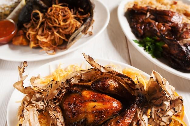 Asortyment niezdrowych potraw z grilla na białym drewnianym stole