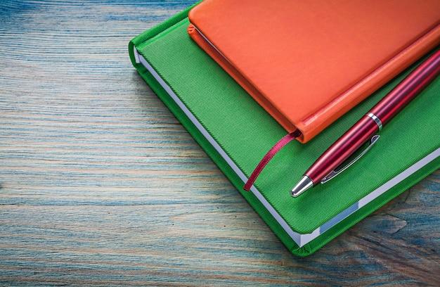 Asortyment notesów i długopisów na drewnianej desce