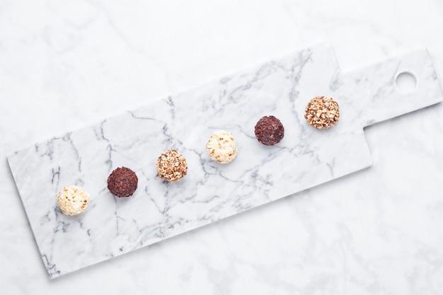 Asortyment odmian luksusowych białych i ciemnych cukierków czekoladowych na tle białego marmuru> widok z góry