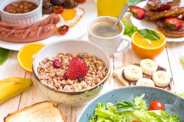 Asortyment opcji śniadaniowych. śniadanie angielskie, kiełbaski, jajka sadzone, bekon, surówka, muesli