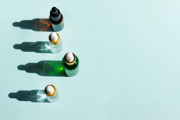Asortyment organicznych kosmetyków spa ze składnikami ziołowymi. serum do pielęgnacji skóry. kosmetyki naturalne w szklanych butelkach z pipetą na niebieskim tle.