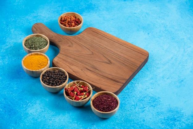 Asortyment organicznych przypraw wokół drewnianej deski.