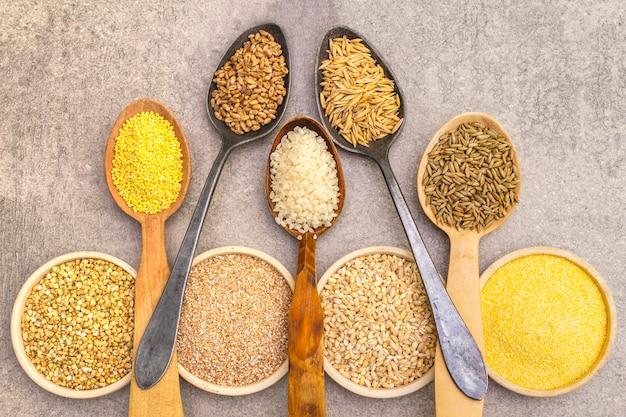 Asortyment organicznych zbóż, roślin strączkowych i produktów pełnoziarnistych w miskach i łyżkach