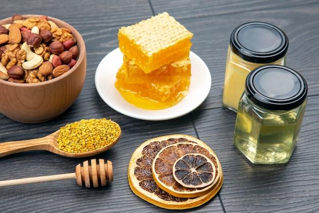Asortyment orzechów i różne suszone owoce cytrusowe i świeży miód kwiatowy o strukturze plastra miodu i pyłek na desce kuchennej. przydatne pokarmy witaminowe dla ludzkiego ciała