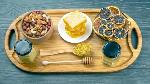 Asortyment orzechów i różne suszone owoce cytrusowe i świeży miód kwiatowy o strukturze plastra miodu na drewnianej desce kuchennej. przydatne pokarmy witaminowe dla ludzkiego ciała