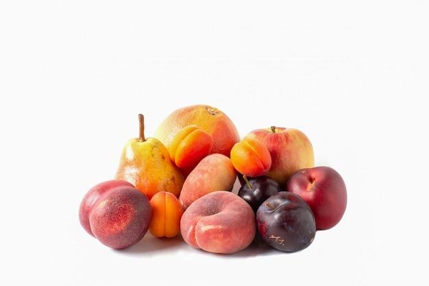 Asortyment owoców na białym tle. gruszka, jabłko, grejpfrut, morele, brzoskwinie i śliwki