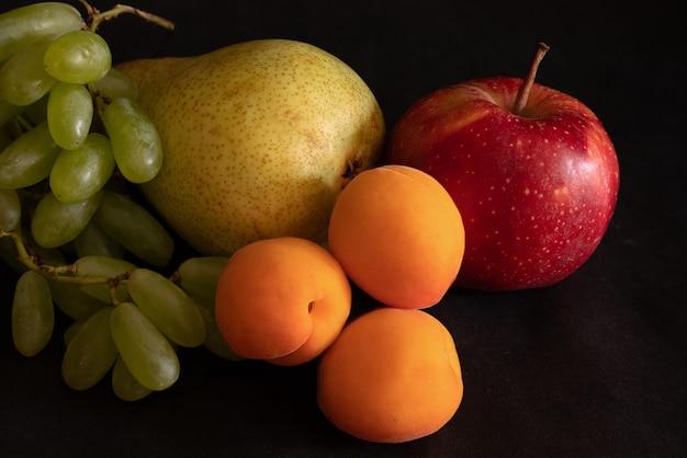 Asortyment owoców świeżych owoców winogrona morele gruszka jabłko na czarnej powierzchni