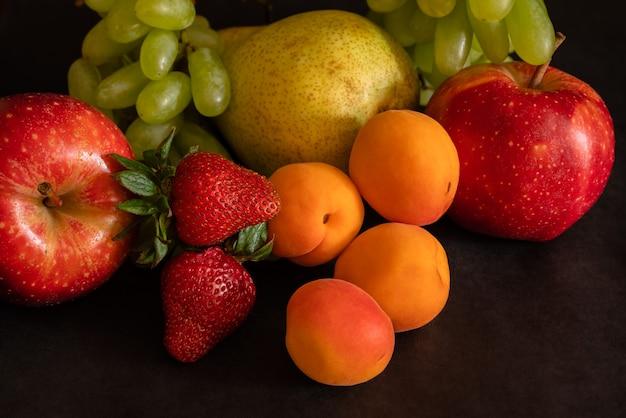 Asortyment owoców świeżych owoców winogrona truskawki morele gruszka jabłko na czarnej powierzchni