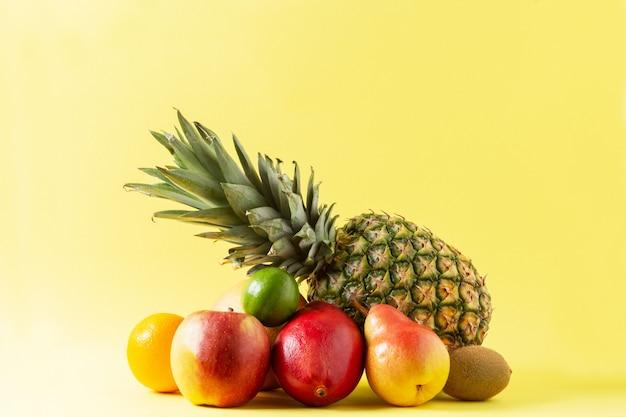 Asortyment owoców tropikalnych na żółtym tle: ananas, jabłko, pomarańcza, gruszka, mango, limonka i kiwi