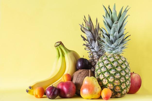 Asortyment owoców tropikalnych na żółtym tle: ananas, kokos, banany, gruszka, morele, brzoskwinia i śliwka.