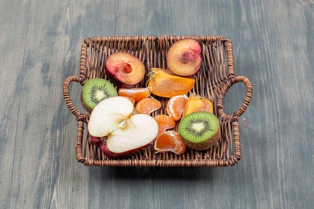 Asortyment owoców w wiklinowym koszu na drewnianym stole