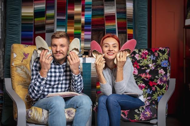 Asortyment. para wybiera tekstylia w sklepie z dekoracjami do domu, sklep. wykonywanie aranżacji wnętrz domowych podczas kwarantanny. szczęśliwy mężczyzna i kobieta, młoda rodzina wyglądają marzycielsko, wesoło dobierając materiały.