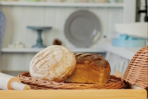 Asortyment pieczywa w pobliżu wiklinowego kosza na stole w rustykalnej kuchni. kompozycja w kuchni w studio fotograficznym