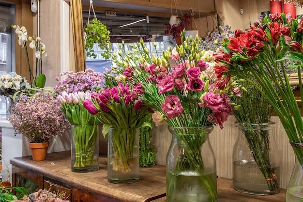 Asortyment pięknych kwiatów w sklepie na sprzedaż, umieszczonych w wazonach w kwiaciarni. tulipany, róże i limonium.