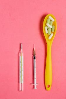 Asortyment pigułki i kapsułki w żółtej łyżce, strzykawka, termometr na różowym tle.