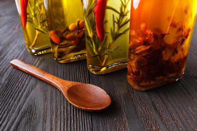 Asortyment pikantnych olejków z ziołami i przyprawami w różnych butelkach