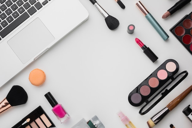 Asortyment produktów płaskich z paletami do makijażu i laptopem