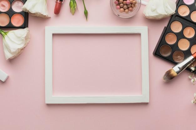 Asortyment produktów płaskich z produktami do makijażu i ramą