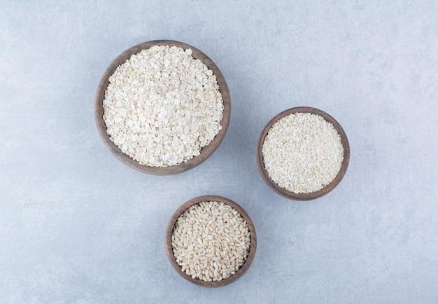Asortyment produktów zbożowych z białego zboża w misach drewnianych na marmurowym tle.