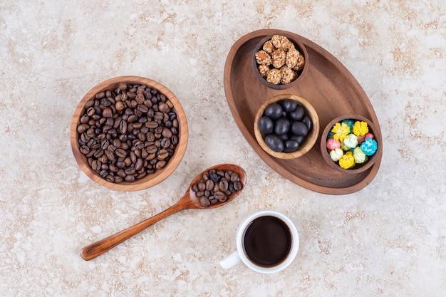 Asortyment przekąsek na drewnianej tacy obok ziaren kawy i filiżanki parzonej kawy