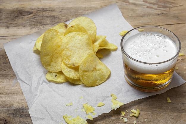 Asortyment przekąsek w domu z chipsami ziemniaczanymi, piwem, krakersami, zielonymi i czarnymi oliwkami na drewnianym stole
