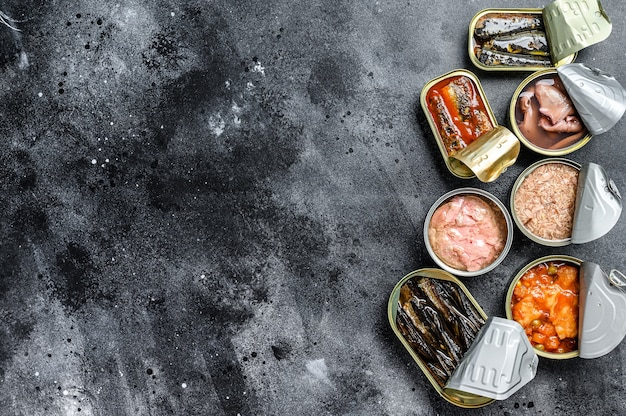 Asortyment puszek konserwowanych z różnymi rodzajami ryb i owoców morza. czarne tło.