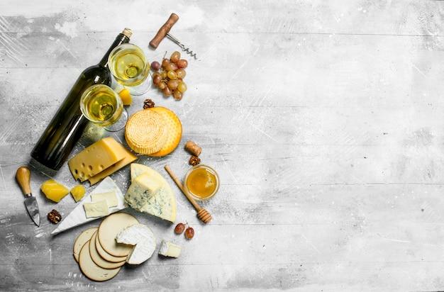 Asortyment rodzajów sera z białym winem i miodem na drewnianym stole.