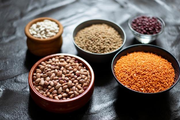 Asortyment roślin strączkowych: fasola i soczewica. surowe zdrowe jedzenie. białko roślinne. ciemne tło ścieśniać. miejsce na tekst