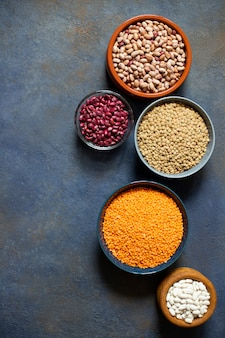 Asortyment roślin strączkowych: fasola i soczewica. surowe zdrowe jedzenie. białko roślinne. ciemne tło widok z góry. miejsce na tekst