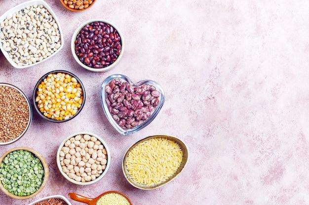 Asortyment roślin strączkowych i fasoli w różnych misach na jasnym kamieniu. widok z góry. zdrowe wegańskie jedzenie białkowe.