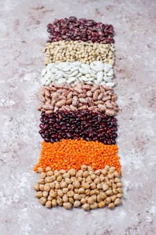 Asortyment roślin strączkowych i fasoli w różnych miskach na jasnym tle kamienia. widok z góry. zdrowe wegańskie białko.