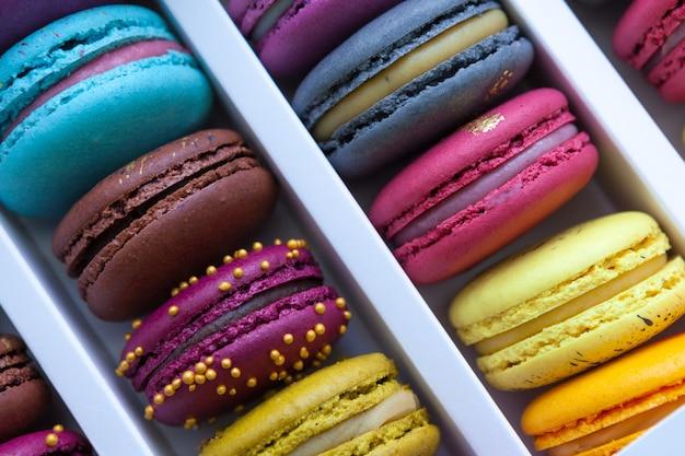 Asortyment różnych kolorowych makaroników leży w tekturowym pudełku