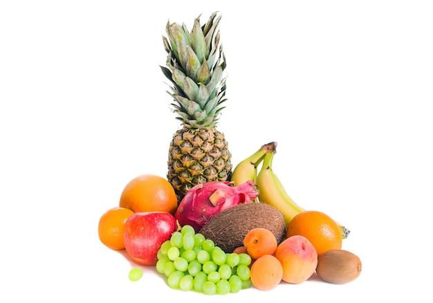 Asortyment różnych owoców na białym tle ananas, banany, pitaja, zielone winogrona, jabłko, kokos, brzoskwinie, morele, mandarynki i kiwi