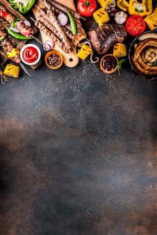 Asortyment różnych potraw z grilla mięso z grilla, festyn grillowy - szaszłyk, kiełbaski, grillowany filet mięsny, świeże warzywa, sosy, przyprawy, ciemny zardzewiały betonowy stół, powyżej miejsca kopiowania