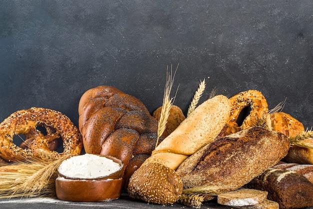 Asortyment różnych pysznych świeżo upieczonego chleba, na czarnej powierzchni betonu widok z góry na miejsce