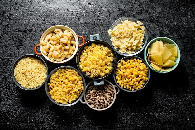 Asortyment różnych rodzajów makaronów suchych w różnych miseczkach na czarnym rustykalnym stole.