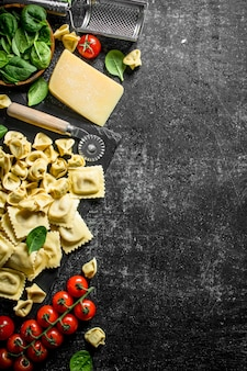 Asortyment różnych rodzajów makaronów surowych z serem, pomidorami i ziołami.