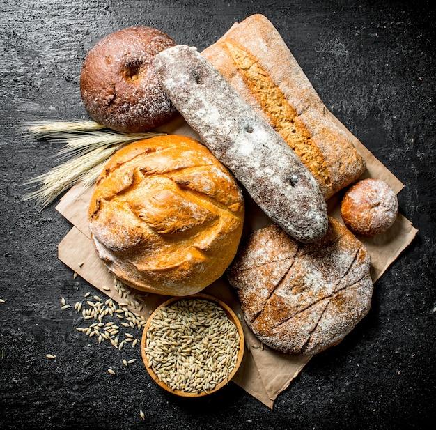 Asortyment różnych rodzajów pieczywa z mąki żytniej i pszennej. na czarnej powierzchni rustykalnej