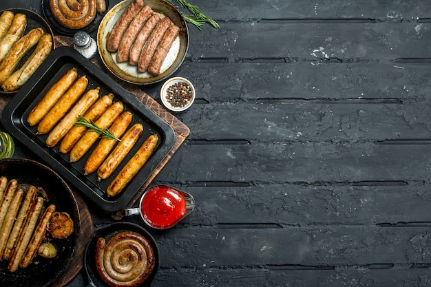 Asortyment różnych rodzajów smażonych kiełbas. na czarnym rustykalnym stole.