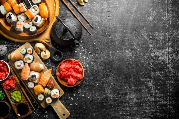 Asortyment różnych rodzajów sushi i bułek. na ciemnej rustykalnej powierzchni