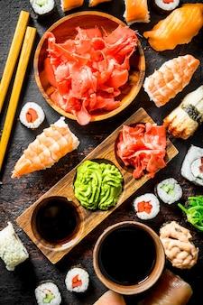 Asortyment różnych rodzajów sushi, rolad i maki. na powierzchni rustykalnej
