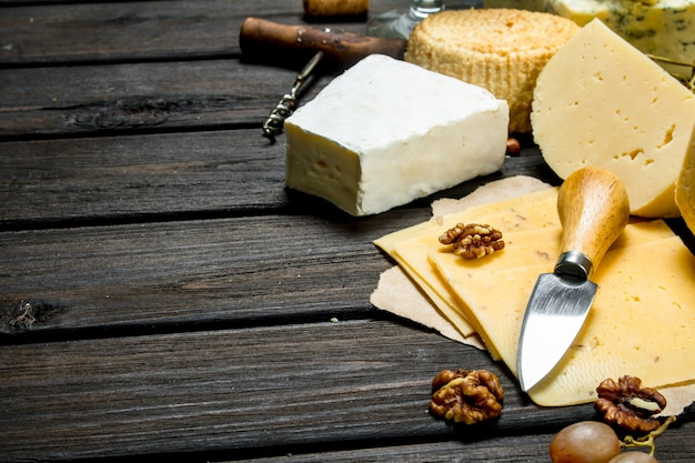 Asortyment różnych serów z winogronami i orzechami włoskimi. na drewnianym.