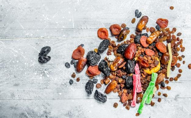 Asortyment różnych suszonych owoców. na rustykalnym stole.
