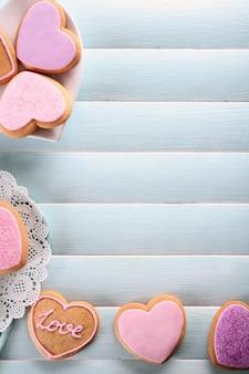 Asortyment różowych ciasteczek miłości na niebieskiej powierzchni drewnianego stołu, kopia przestrzeń