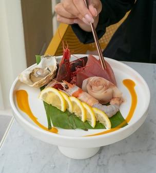 Asortyment sashimi z marakui na białym talerzu na białym tle poza restauracją