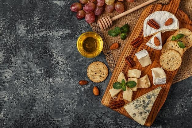 Asortyment sera z miodem, orzechami i winogronami na desce do krojenia.