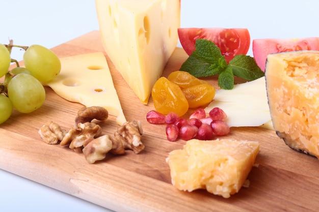 Asortyment sera z owocami, winogronami, orzechami i nożem do sera na drewnianej tacy.